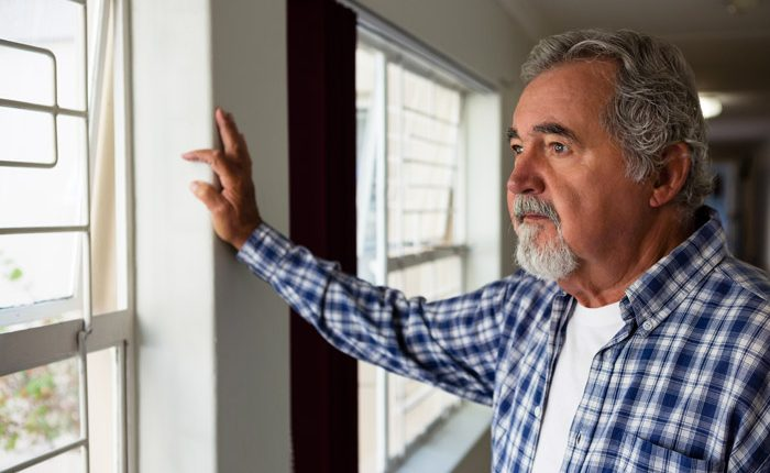 senior man with sad look on his face, looking out the window of his home - major depression