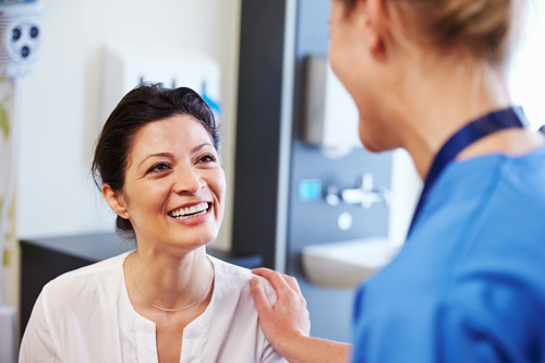 smiling female patient talking to female nurse or doctor