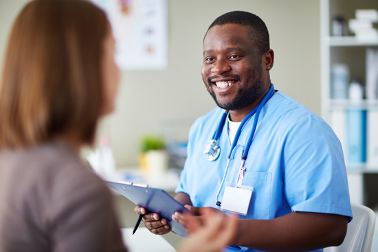 smiling Black male nurse or doctor talking to female patient