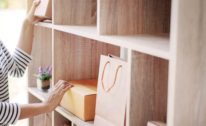 cropped shot of woman using wooden wall cubby to organize room - decluttering